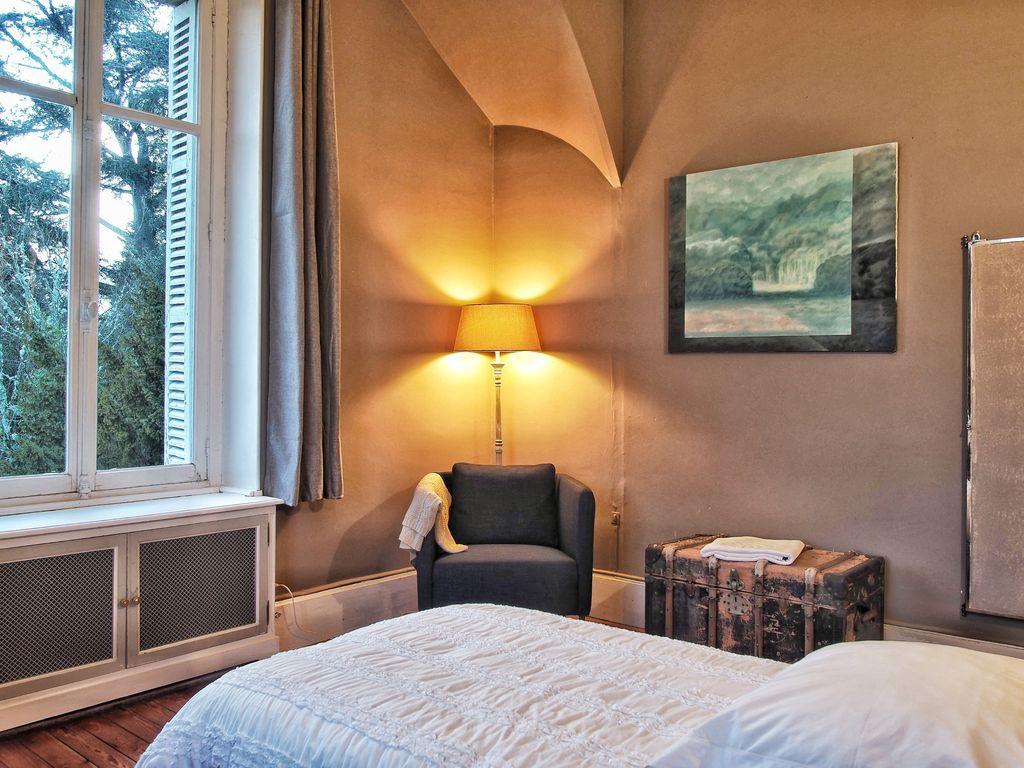 chambre grise avec un lit et une grande fenêtre donnant sur les exterieurs du manoir